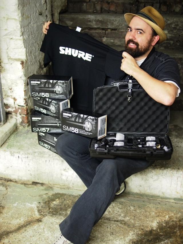 Gus Rodriguez, delighted to unpack a box from Shure electronics that contained an assortment of their best vocal, instrumental and percussion microphones.